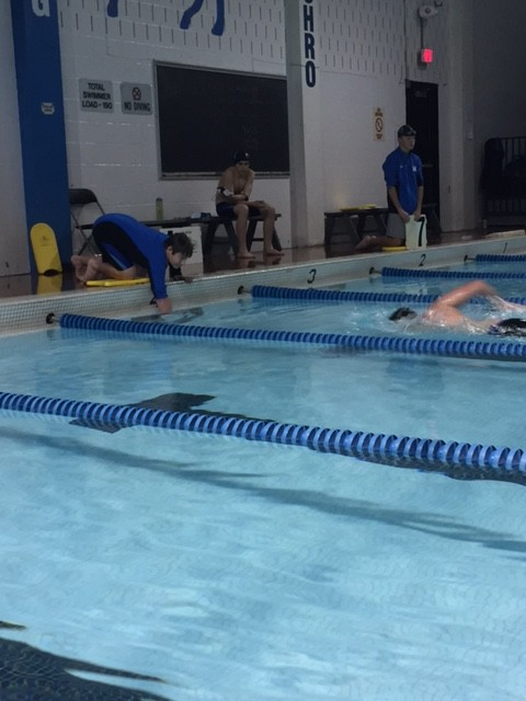 Ian Girod, freshman, counts laps as Nick Leebens, senior captain, races in the 500 yard freestyle.
