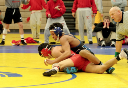 Nate Johnson, junior, attempts to pin down his opponent.