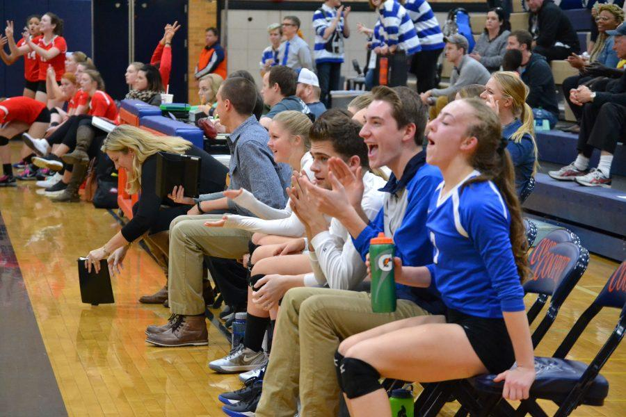 Joe Swenson, and Bryce Walker, senior volleyball managers, sit beside the  players during a match this past fall