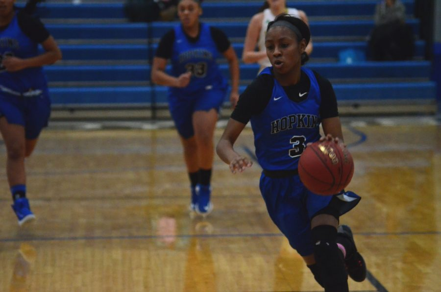 Reana Suggs, junior, dribbles towards the hoop during the game.