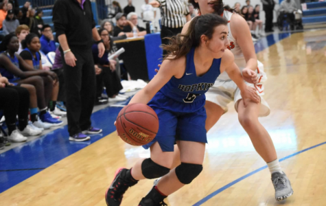 Asha Bozicevich, senior, dribbles ball past defender. The Royals beat the Warriors 72-58.