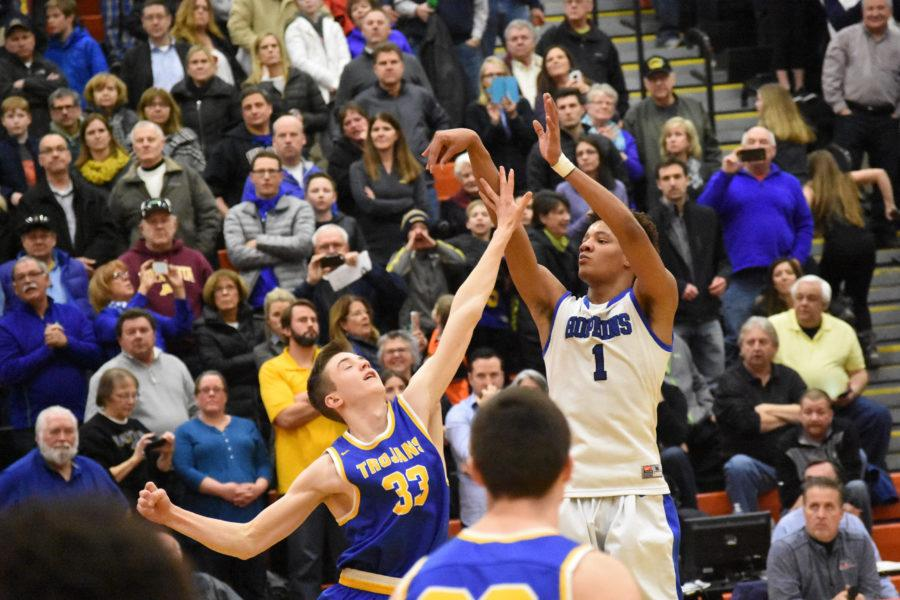 Ish El-Amin, senior, shoots three pointer in the face of Wayzata defender. The Royals fell to the Trojans in the 6AAAA section finals 51-66.