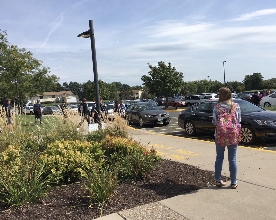 Cars of parents line up waiting for students as other cars try to evacuate.