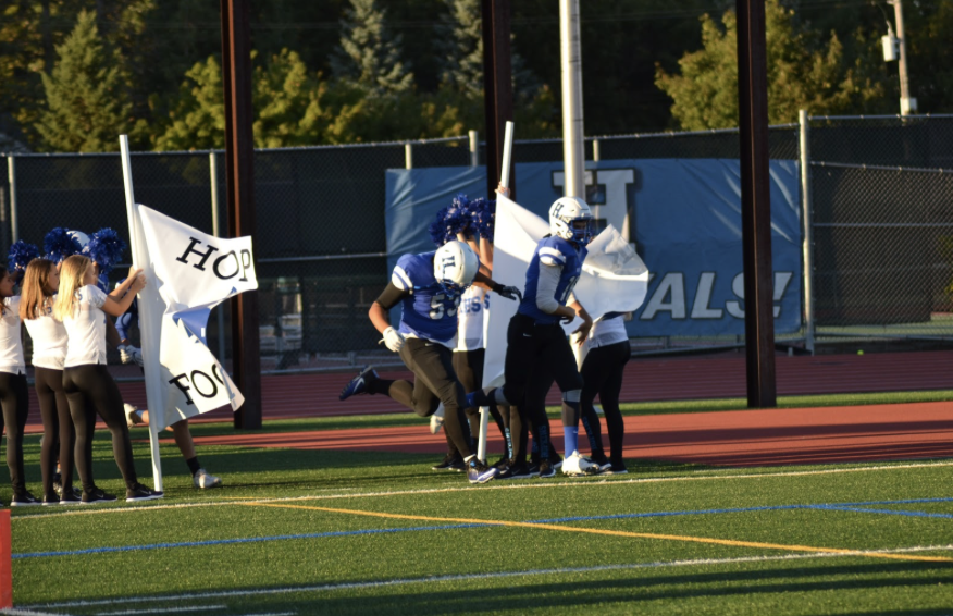 Paul Madison, senior, and James Klecker, junior, break through a banner before their first home game. The Royals are now 0-3 after a tough loss the the falcons.