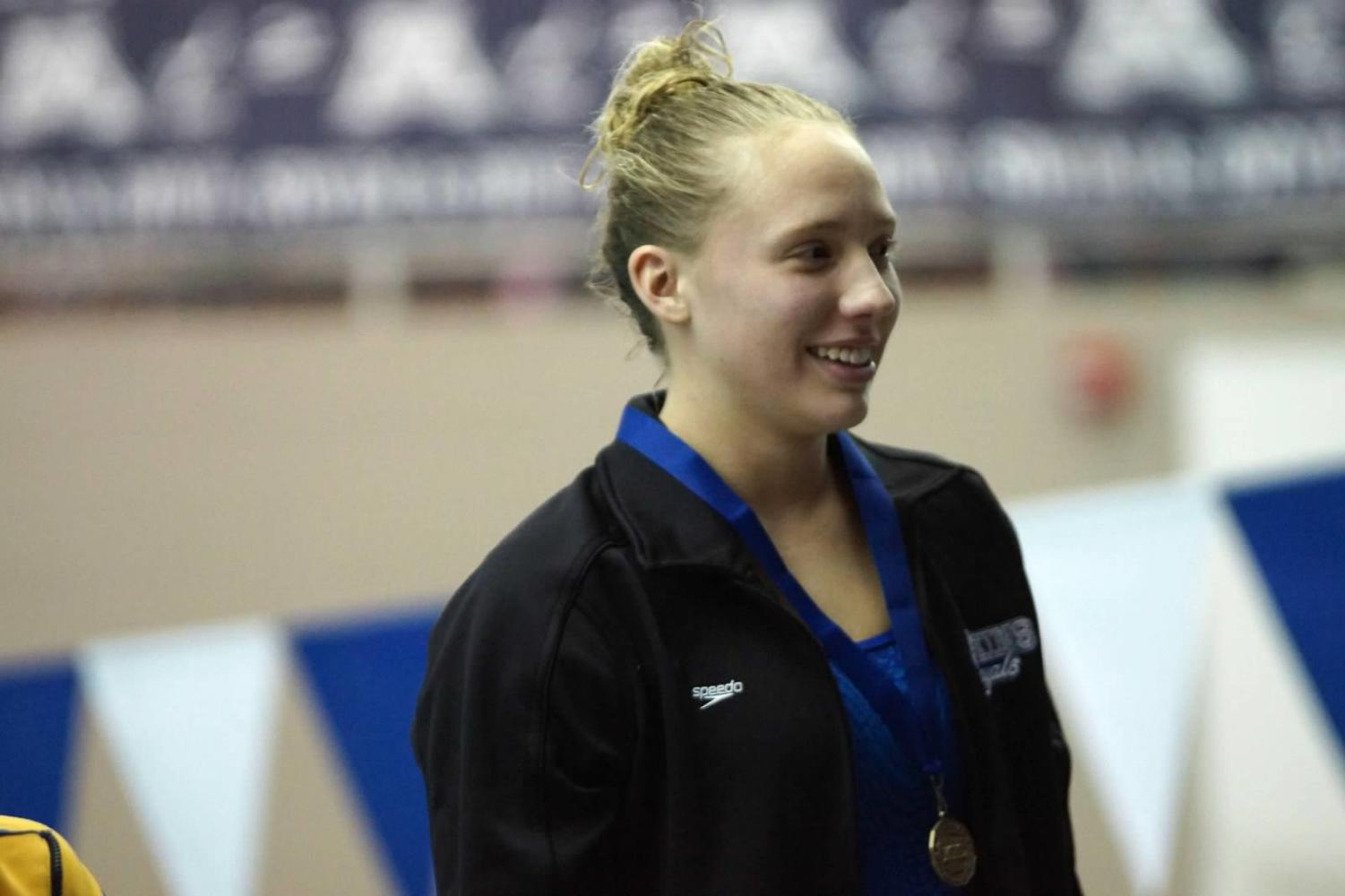 Susanna Fish, junior, on podium after winning section title in diving. Fish qualified for state.