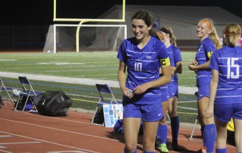 Josie Fieldman, senior, runs up to greet her parents during the halftime ceremony honoring seniors.