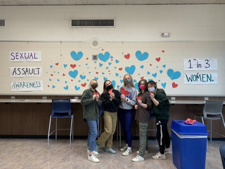 Five HHS seniors pose in front of their mural created in honor of Sexual Assault Awareness Month