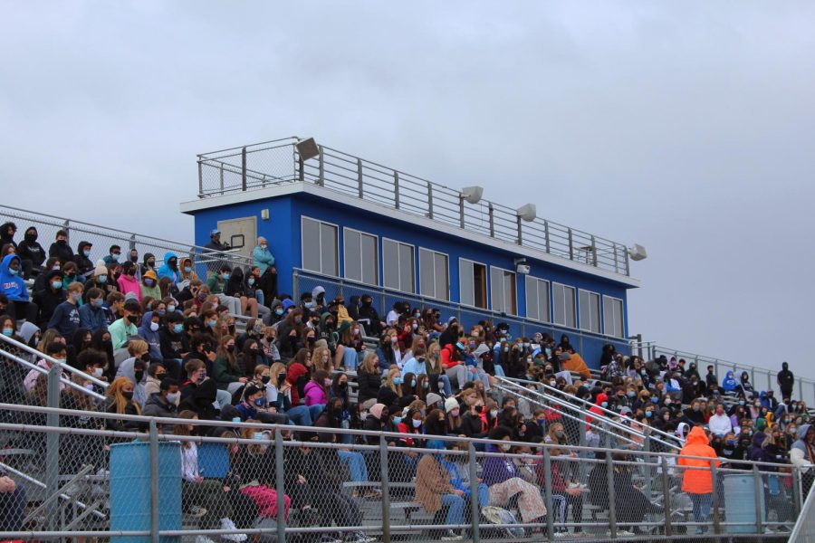 Hundreds of students sit in the bleachers and listen to students on the track.